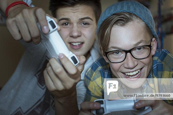 Zwei Teenager Jungen spielen zusammen Videospiel