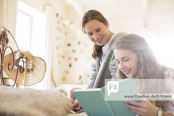Zwei Teenager-Mädchen lesen zusammen im Bett.