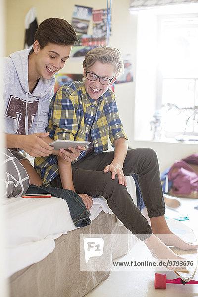 Zwei Teenager-Jungs teilen sich ein digitales Tablett im Zimmer