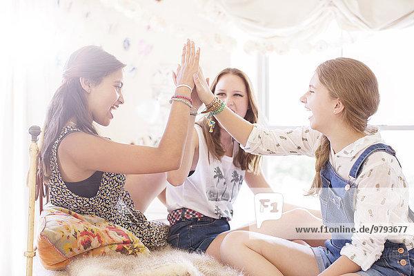 Drei Teenager-Mädchen, die High Five im Bett machen.