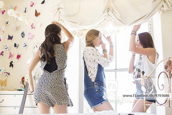 Drei Teenager-Mädchen tanzen auf dem Bett im Schlafzimmer.