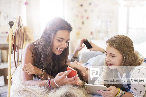 Drei jugendliche Mädchen, die elektronische Geräte benutzen, während sie auf dem Bett liegen.