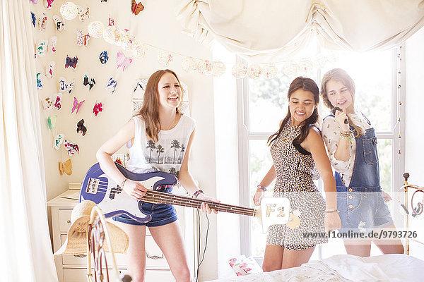 Drei Teenager-Mädchen beim Musizieren und Singen im Schlafzimmer