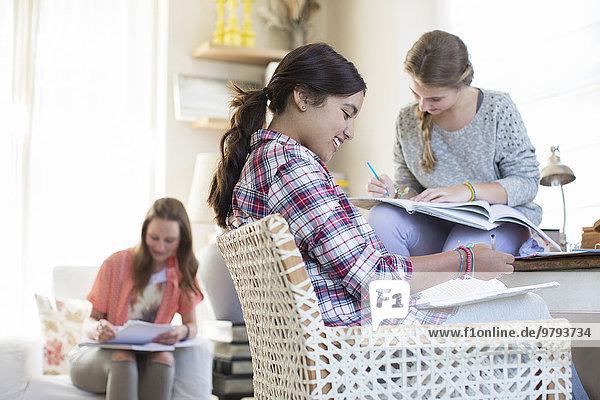 Drei Teenager-Mädchen bei den Hausaufgaben im Zimmer
