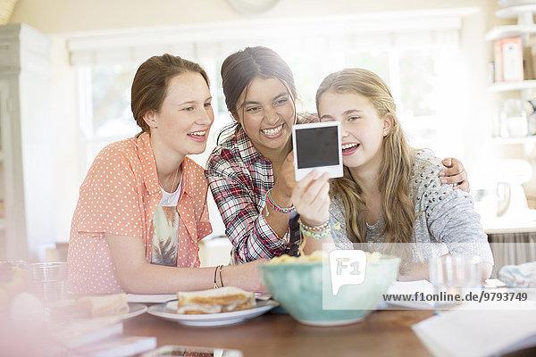 Drei Mädchen im Teenageralter, die beim Sitzen am Tisch ein Foto ansehen