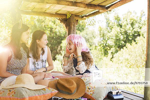 Drei Teenager-Mädchen spielen im Sommer im Baumhaus