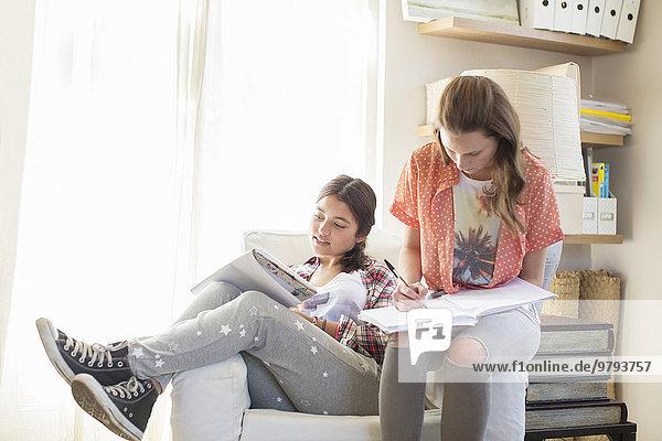 Zwei Teenager-Mädchen bei den Hausaufgaben im Zimmer