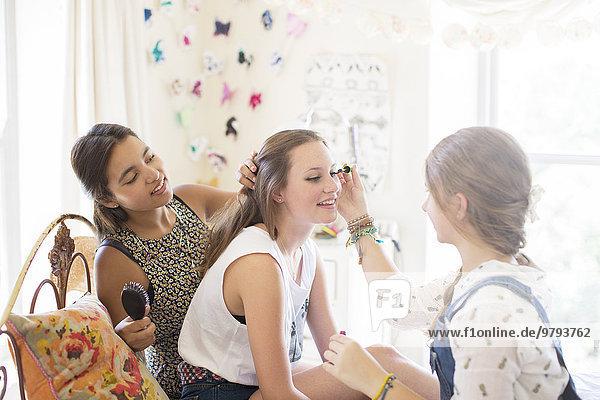Drei Teenagermädchen beim Schminken und Haareputzen im Schlafzimmer