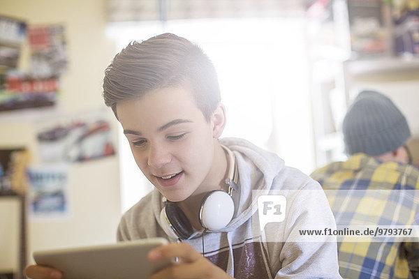 Zwei Teenager, die im Zimmer sitzen und elektronische Geräte benutzen.