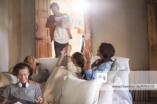 Gruppe von Jugendlichen wartet auf Pizza im Wohnzimmer