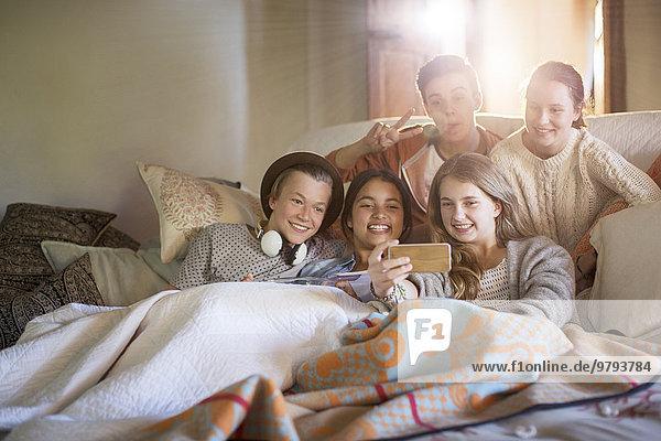 Gruppe von Teenagern  die sich auf dem Sofa im Wohnzimmer niederlassen.