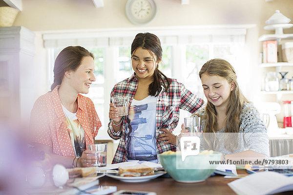 Drei Teenager-Mädchen beim Trinken und Essen am Tisch in der Küche