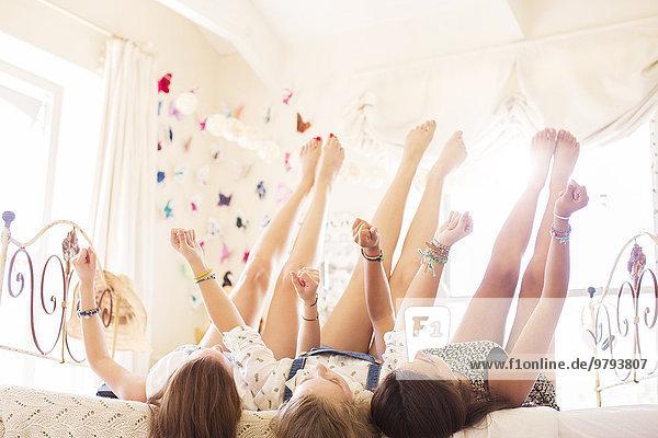 Drei Teenager-Mädchen liegen mit erhobenen Füßen auf dem Bett.