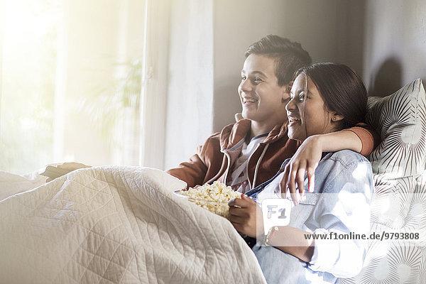 Teenager-Paar im Bett liegend und fernsehend