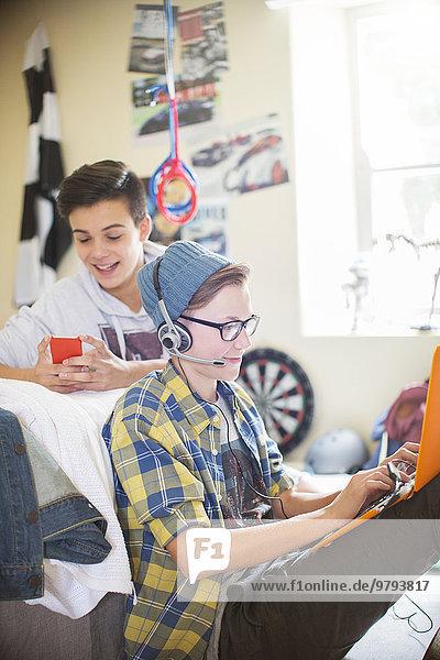 Zwei Teenager, die elektronische Geräte im Zimmer benutzen.