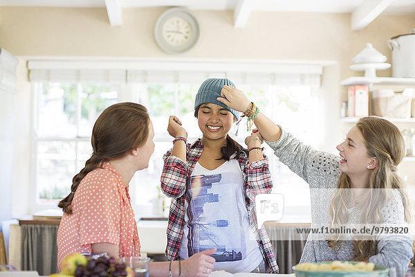 Drei Teenager-Mädchen spielen mit Mütze im Esszimmer