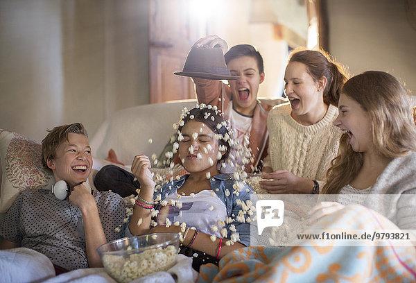 Gruppe von Jugendlichen, die Popcorn auf sich selbst werfen, während sie auf dem Sofa sitzen.