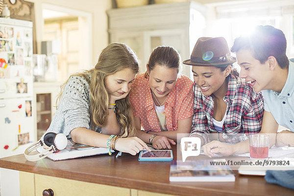 Gruppe von Teenagern  die gemeinsam ein digitales Tablett am Tisch in der Küche benutzen.