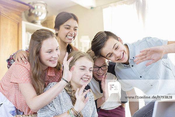 Gruppe von Teenagern  die bei der Kommunikation über das Internet winken