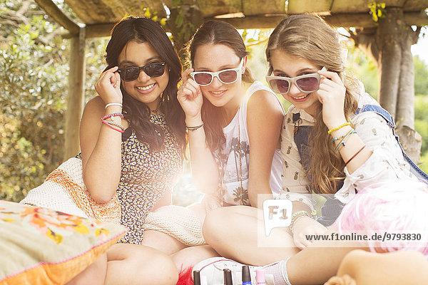 Porträt von drei Teenagern mit Sonnenbrille und im Baumhaus sitzend