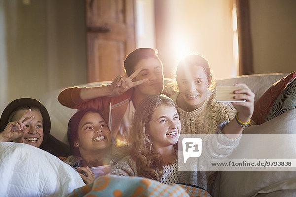 Gruppe lächelnder Teenager auf dem Sofa im Wohnzimmer