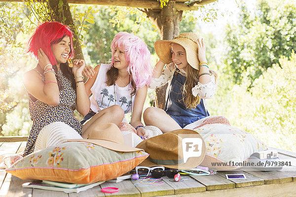 Drei Teenagermädchen mit Perücken und Hut, die im Sommer im Baumhaus sitzen.