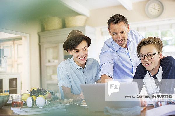 Mittlerer erwachsener Mann mit Teenagern  die einen Laptop in der Küche benutzen.