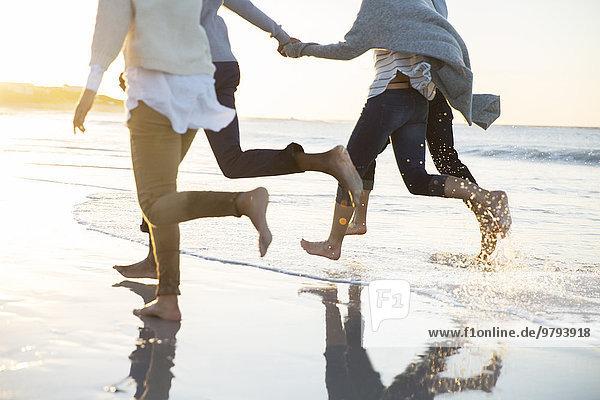 Gruppe von vier Freunden  die Händchen halten und am Strand rennen.