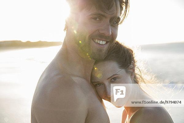 Porträt eines jungen Paares  das sich am Strand umarmt