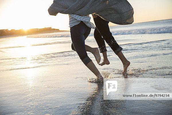 Beine eines jungen Paares  das bei Sonnenuntergang am Strand läuft.