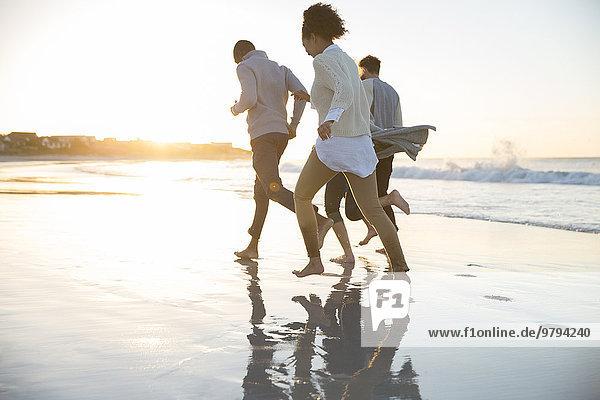 Vier Freunde beim Laufen am Strand in der Abendsonne