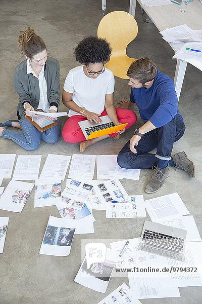 Drei junge Leute sitzen auf dem Boden und arbeiten zusammen im Studio.