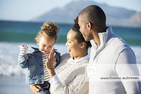 Glückliche Familie gibt High Five am Strand