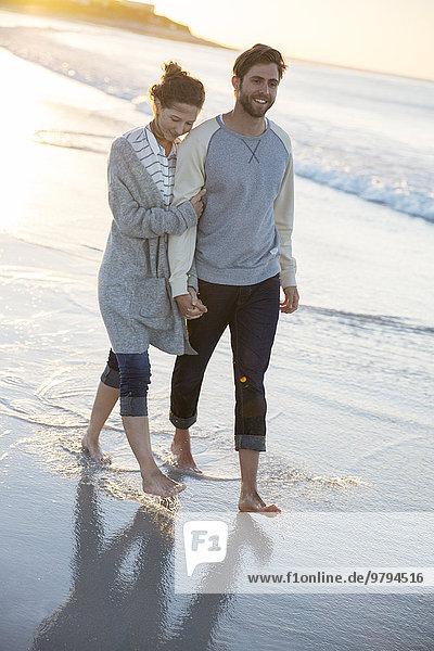 Junges Paar beim Strandspaziergang in der Abendsonne