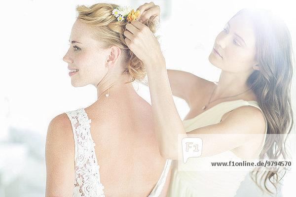 Brautjungfer hilft Braut mit Frisur im Garten