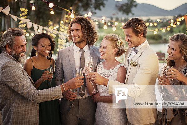 Junges Paar und seine Gäste mit Champagnerflöte bei der Hochzeitsfeier im Garten