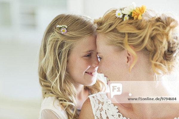 Braut und Brautjungfer einander gegenüber lächelnd
