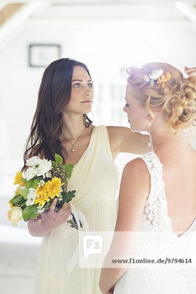 Brautjungfer hilft Braut mit Frisur im Schlafzimmer