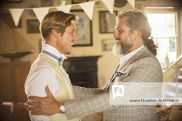 Trauzeuge und Bräutigam stehend und lachend im häuslichen Raum