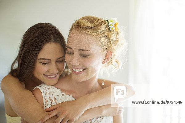 Brautjungfer umarmt Braut im Schlafzimmer