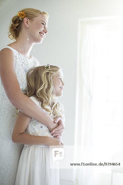 Braut umarmt Brautjungfer und schaut aus dem Fenster.