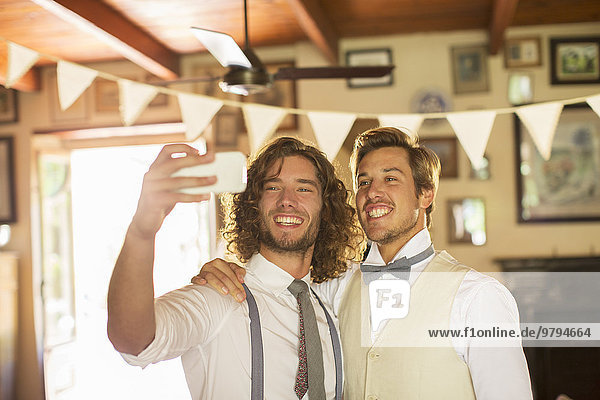 Bräutigam und Trauzeuge beim Selbstfotografieren im Wohnzimmer