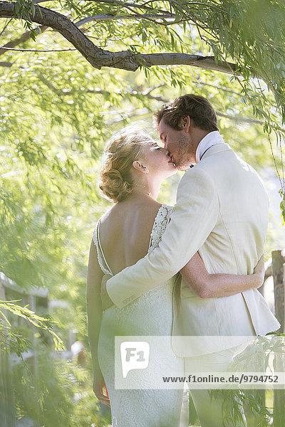 Junges Paar beim Küssen im Hausgarten