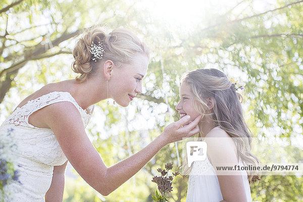 Braut und Brautjungfer einander gegenüber im Hausgarten beim Hochzeitsempfang