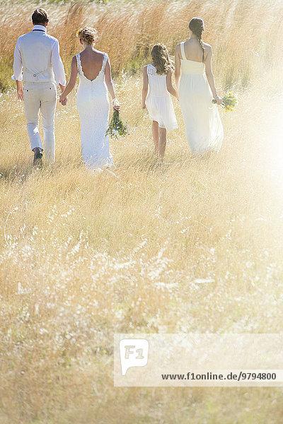 Junges Paar mit Brautjungfer und Mädchen  die auf der Wiese spazieren gehen