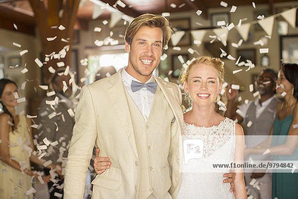 Porträt eines lächelnden jungen Paares im fallenden Konfetti während des Hochzeitsempfangs