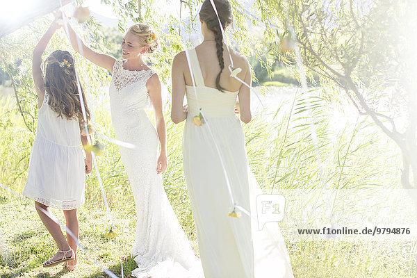 Braut und Brautjungfer spielen mit Dekorationen im Hausgarten während des Hochzeitsempfangs