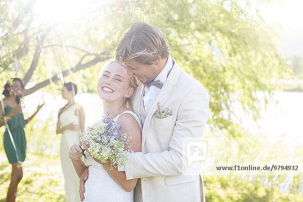Junges Paar mit Blumenstrauß bei der Hochzeitsfeier im Hausgarten