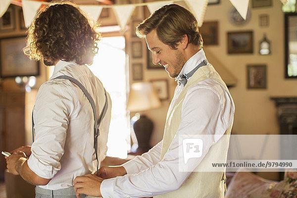 Bräutigam und Trauzeuge bei der Vorbereitung der Trauung im häuslichen Raum
