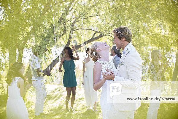 Junges Paar tanzt bei der Hochzeitsfeier im Hausgarten